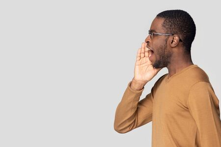 Serious young African American man in glasses speaking loud, shouting aside at copy space, making advertisement, announcement, holding hand near open mouth, isolated on grey background