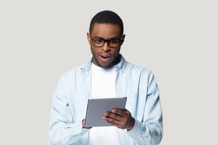 Head shot close up surprised African American man looking at computer tablet screen, young male using electronic device, reading unexpected news in email, shopping offer, isolated on grey background Stockfoto