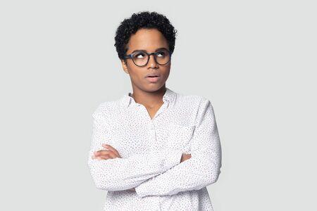 Retrato de disparo a la cabeza de cerca molesta mujer afroamericana con gafas rodando los ojos, niña decepcionada con los brazos cruzados irritada por las malas noticias del trabajador de rutina aburrido, aislado sobre fondo gris Foto de archivo