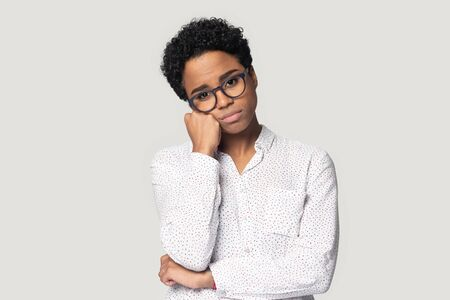 Head shot portrait close up bored African American girl in glasses touching chin, sad woman looking at camera, lack of motivation and energy, suffering from idleness, isolated on grey background Banque d'images