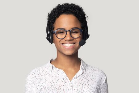 Head shot portrait close up smiling African American woman in glasses, support service operator in wireless headphones with microphone looking at camera, satisfied worker, isolated on grey background Banque d'images - 132554207