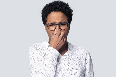 Head shot portrait close up unhappy African American young woman in glasses closing nose, upset girl looking at camera, suffering from disgusting bad smell, isolated on grey background