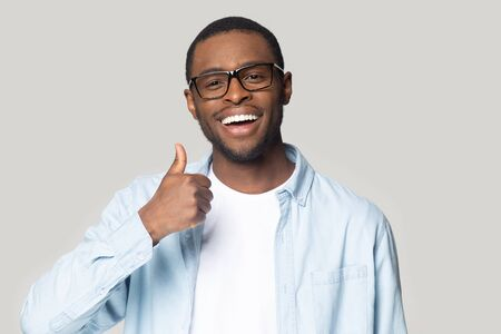 Head shot happy excited African American man in glasses showing thumbs up, handsome young male with healthy toothy smile looking at camera, customer recommending service, isolated on grey background Banque d'images - 132554320