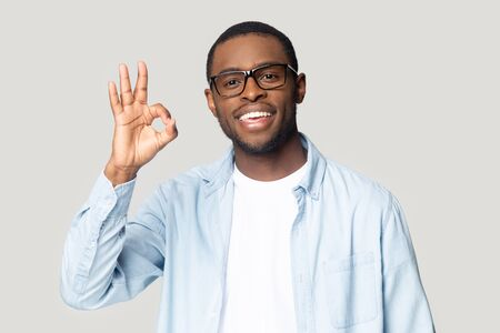 Head shot portrait close up happy African American man in glasses showing ok gesture isolated on grey studio background, satisfied customer, excited young male with healthy smile looking at camera Banque d'images - 132554452