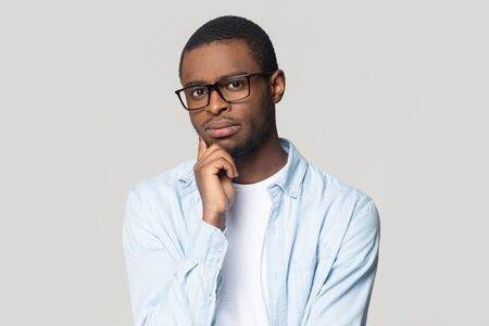 Head shot portrait puzzled African American man wearing glasses pondering idea, looking at camera, touching chin, thoughtful worker, student planning future, isolated on grey studio background Banque d'images - 132554311