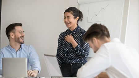 Attractive emotional young Indian leader coach woman laughing at unexpected colleagues joke. Millennial multiethnic business team having fun together during working process, office meeting training.