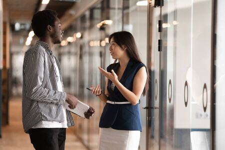 African American businessman and Asian businesswoman talking in modern office hallway, diverse colleagues having pleasant conversation during break, sharing ideas, discussing project Stock fotó