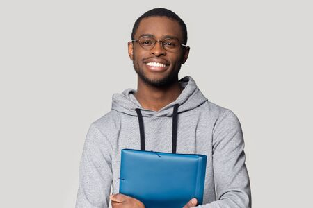 Head shot portrait smiling African American man in glasses holding folder for papers with documents, happy handsome student, worker looking at camera, posing for photo isolated on grey background Banque d'images - 132558047