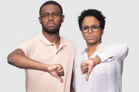 Retrato de disparo en la cabeza de cerca infeliz pareja afroamericana en gafas mostrando los pulgares hacia abajo, mirando a la cámara, hombre y mujer insatisfechos dando retroalimentación negativa, aislado sobre fondo gris