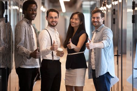 Portrait smiling diverse employees standing in office hallway, showing thumbs up, recommending service, motivated for business success, looking at camera, posing for company photo together Zdjęcie Seryjne