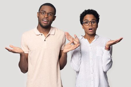 Head shot portrait close up shocked African American man and woman in glasses shrugging shoulders, lifting hands, feeling confused, puzzled young couple looking at camera, isolated on grey background Stock Photo