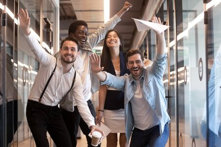 Portrait happy diverse employees celebrating business victory, excited team having fun at corporate party, smiling and laughing colleagues looking at camera, standing in modern office hallway Banque d'images - 132558171