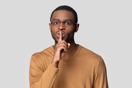 Head shot portrait close up funny African American man in glasses showing hush gesture isolated on grey studio background, keeping finger on lips, privacy, secret private information, sign of silence Banco de Imagens