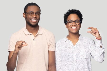 Head shot portrait close up happy African American couple in glasses showing little size gesture, looking at camera, winking, shopping sales discount, small prices, isolated on grey background