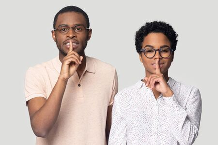 Head shot portrait close up African American man and woman in glasses showing hush gesture, isolated on grey background, keeping finger on lips, privacy, secret private information, sign of silence Banco de Imagens