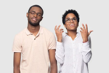 Head shot bored African American man listening to excited smiling woman, bad conversation, beautiful girlfriend talking to boyfriend, friends wearing glasses standing isolated on grey background