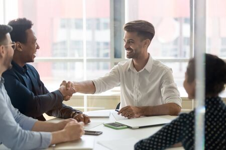 Multiethnic smiling young work team greeting each other, celebrate good deal, welcome new employee at work meeting in company board room. White collar workers start new project negotiations, shake hands