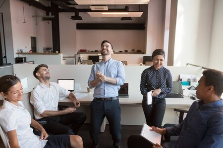 Millennial overjoyed successful diverse team laugh loudly at shared office. Happy male leader joking, having fun with multiracial teammates over african american coworker.