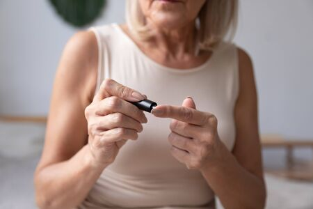 Diabetic mature woman hold use blood glucose meter in bedroom, old senior adult lady check morning insulin sugar level test with glucometer lancet on finger, diabetes diagnostic concept close up view Banque d'images