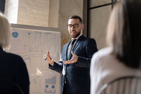 Smiling businessman coach manager trainer wear suit give business flip chart presentation conduct conference training, confident male speaker presenter speaking during office workshop meeting concept