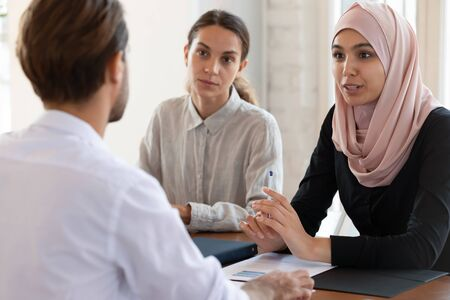 Asian muslim female hr manager interviewing job applicant consulting male client at diverse group meeting negotiations, ethnic businesswoman wear hijab speaking to partner, human resource concept Stock Photo