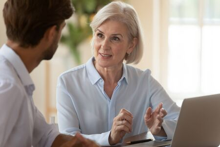 Middle aged old businesswoman manager mentor speaking to businessman client offering insurance banking services deal teaching intern or convincing customer at business office meeting sit at table.