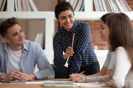 Indiase leraar legt educatieve materiële taak uit aan multinationale groep studenten, concept van ondersteuning en hulp, studieproces, kennis opdoen, ideeën delen en samen denken over gemeenschappelijke oefeningen