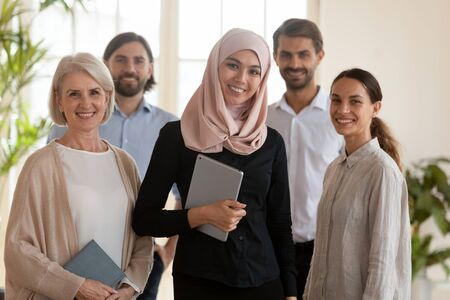 Confident happy young asian muslim professional businesswoman manager boss leader wear hijab and multicultural office team people staff group standing together in modern office, corporate portrait