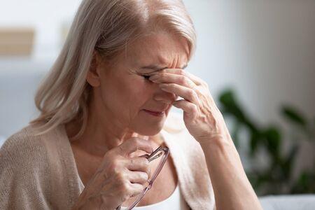 Stanco sconvolto donna di mezza età più anziana che si toglie gli occhiali strofinando gli occhi asciutti massaggiando le palpebre sensazione di affaticamento degli occhi concetto di affaticamento, esausta signora anziana matura soffre di problemi di vista del dolore alla vista