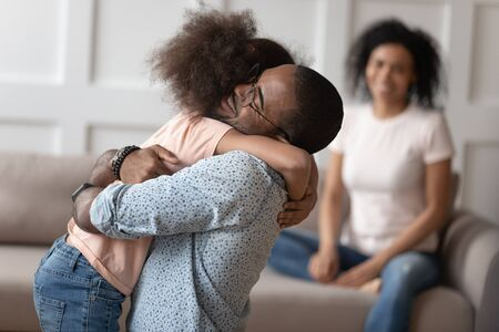Happy little biracial girl hug loving african American dad meeting him at home after work business trip, overjoyed mixed race kid embrace black father reunited with smiling mom. Family reunion concept