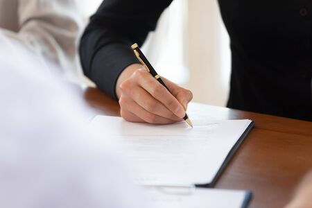 Male customer client write signature on business document sign contract agreement on table make commercial financial sale purchase deal buy insurance doing paperwork management concept, close up view 免版税图像