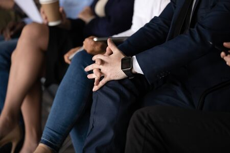 Stressed nervous unemployed businessman wear suit sit on chair with clasped hands waiting in business people hr applicants group row waiting for job interview, human resource concept, close up view