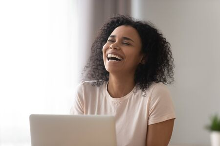 Happy African American woman laughing at funny joke in social network or video close up, using laptop, chatting with friends online, beautiful girl with healthy smile having fun at workplace Reklamní fotografie