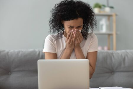 African American woman blowing her running nose, holding handkerchief, sneezing at home, sitting on sofa, unhealthy female freelancer or student using laptop, allergic reaction or seasonal infection