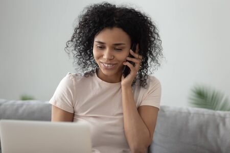 Smiling African American woman talking on cellphone at home, sitting on couch, beautiful girl having pleasant cellphone conversation with friend, hearing good news, making or answering call close up