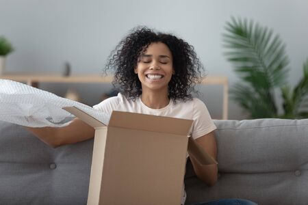 Smiling African American woman unboxing parcel, sitting on couch at home, excited girl removing bubble wrap, satisfied client received online store order, good delivery service concept Stock fotó