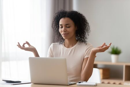 Calm African American woman meditating at desk with laptop, female working or studying at home, beautiful girl with closed eyes doing yoga exercise, breathing deep, stress relief concept
