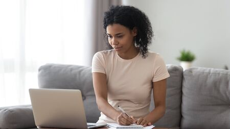 Focused African American woman using laptop, looking at screen, making notes, preparing to pass exam at home, serious girl sitting on couch, doing homework, learning online, watching webinar