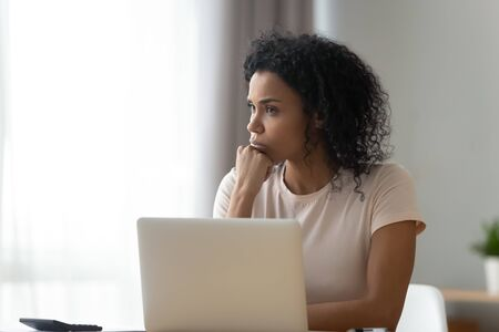 Thoughtful African American woman using laptop, pondering task or strategy, looking in distance, student freelancer working on difficult project at home, pensive girl taking break, planning