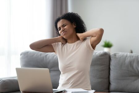 Unhappy African American woman takes break, massaging stiff neck muscles, upset girl suffering from pain after sedentary work with laptop in incorrect posture, sitting on sofa at home Stockfoto