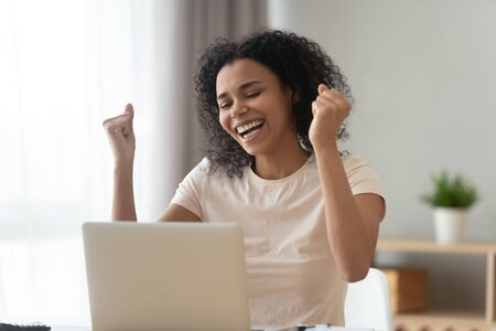Overjoyed African American woman excited by online success, looking at computer screen, using laptop at home, surprised girl reading good news, get job or promotion, positive exam result in email Stok Fotoğraf