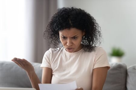 Unhappy angry African American woman reading paper letter, receive bad news, annoyed girl looking at document, debt, bills or taxes, frustrated student with exam result notification close up