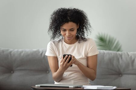 Beautiful African American woman using phone, browsing mobile device apps, attractive girl chatting in social network with friends, checking email, playing game on phone, typing message Reklamní fotografie