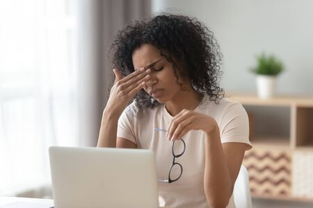 Tired African American woman taking off glasses, feeling eye strain after long laptop use, unhappy girl, student, freelancer suffering from dry eyes syndrome, vision health problem concept