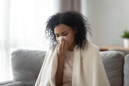 Sick African American woman covered warm blanket blowing running nose, feeling bad, suffering from fever, holding handkerchief, allergic reaction or seasonal infection, problem with health