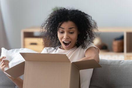 Mujer afroamericana sorprendida desempacando el paquete en casa de cerca, niña sorprendida con los ojos bien abiertos y la boca mirando en una caja de cartón, el cliente satisfecho recibió el pedido de la tienda en línea, el concepto de entrega Foto de archivo