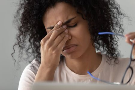 Unhappy African American woman taking off glasses close up, feeling eye strain, tired exhausted female worker, student, freelancer suffering from dry eyes syndrome, vision health problem concept