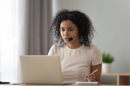 Focused African American woman in headset using laptop, writing notes, watching webinar, student in headphones with microphone learning language online, listening translating lecture course