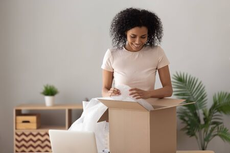 Sonriente mujer afroamericana desempacando el paquete, niña feliz quitando el plástico de burbujas, mirando en la caja de cartón, el cliente satisfecho recibió el pedido de la tienda en línea, buen concepto de servicio de entrega