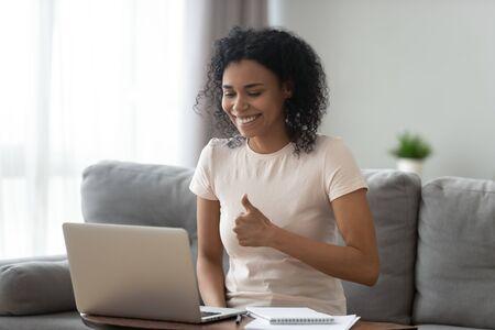 Glimlachende Afro-Amerikaanse vrouw die duimen opsteekt, laptop gebruikt, videogesprek voert, tevreden student die afstandsonderwijs aanbeveelt, leraar mentor webinar opneemt, thuis online werkt Stockfoto